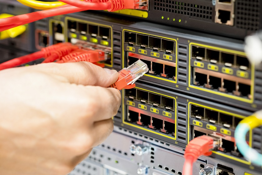 Hand Plugging Fiber Cable Into Switch In Datacenter